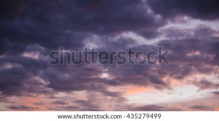 Amazing colored stormy sky with dark clouds moving in the sunset rays - stock photo