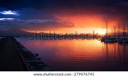 Amazing colors of sunset in the port with reflections of calm sea - focus is on the horizon - stock photo