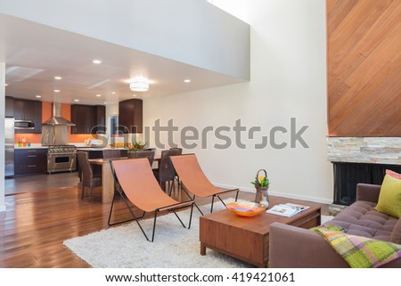 Amazing contemporary living room with hardwood floors and vaulted ceiling in new luxury home. View of Kitchen, entryway, and second story loft style area. - stock photo