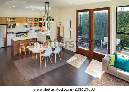 Amazing contemporary luxurious home with kitchen, table in contemporary home with large windows and double french doors surrounded by trees. Hardwood floor with hand-woven natural fine sisal rug. - stock photo