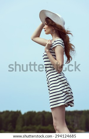 amazing fashion shot of a young woman in white dress with hat , she is in the wind and has windly long hair , sunny day - stock photo