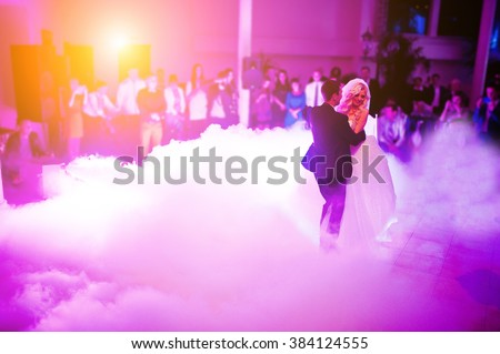 Amazing first wedding dance of newlyweds on low pink light and heavy smoke.  Photo with noise - stock photo