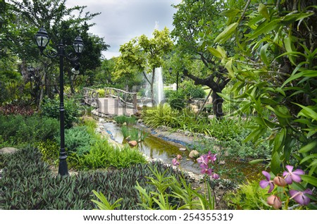 Amazing garden with wooden bridge, canal, orchards, lush green trees and grass and street light