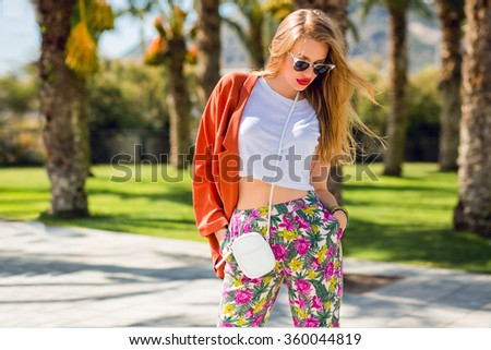Amazing glamour  blonde  woman in trendy summer outfit posing outdoor palm trees background. Bright make up, orange jacket, sunglasses, bag in hands. Fashionable model walking on Miami coast . - stock photo