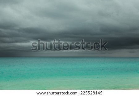 Amazing, gorgeous view of horizon line and upcoming rain storm with dark, dramatic grey cloudy sky above tranquil azure  Atlantic ocean at Cuban Santa Maria island - stock photo