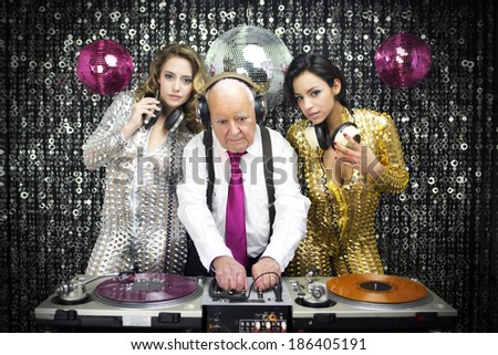 amazing grandpa DJ and his two beautiful gogo dancers - stock photo