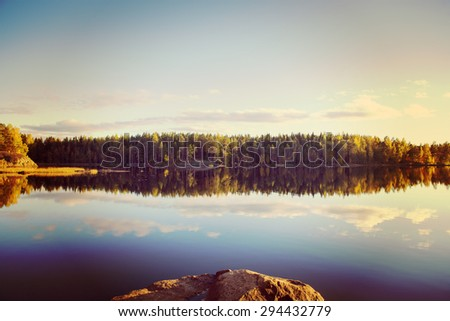 Amazing lake view scenery from Finland during the late night in the summer. Water has a nice reflection. Image has a vintage effect applied. - stock photo