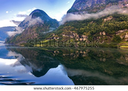 Amazing landscape of nature. Natural wonders, mountains, fjords and forests. Colors seem very beautiful. Mountains and sea can seen between clouds and fogs. Flam, Norway