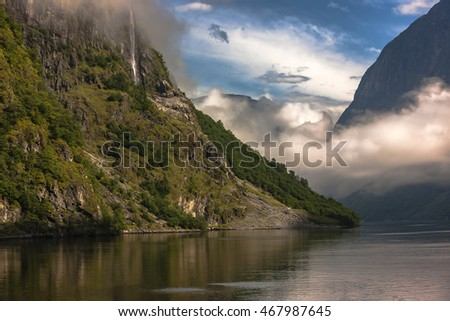 Amazing landscape of nature. Natural wonders, mountains, fjords and forests. Colors seem very beautiful. Sunlight reflect on mountains and clouds. Reflections and shades on sea. Flam, Norway