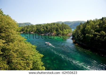 Amazing landscape of norwegian nature with river and small boat - stock photo