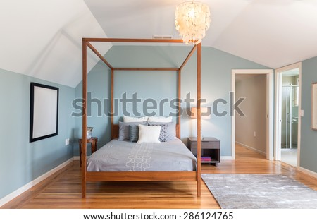Amazing light blue master bedroom with canopy bed frame, softly textured wall paper, designer light with rug and wooden floor.  - stock photo