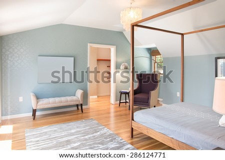 Amazing light blue master bedroom with canopy bed frame, softly textured wall paper, designer light with chair, bench and huge walk in closet. - stock photo