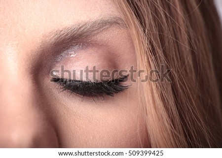 Amazing makeup with stylized eyebrows glowing lid and black mascara