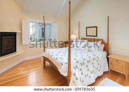 Amazing master bedroom with canopy bed frame, windows with shutters, fire place, wooden night stands and wooden floor. - stock photo