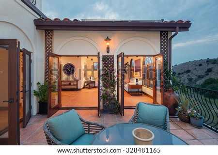 Amazing Mediterranean home at twilight with patio and open double french doors leading to interior. Spanish style home at twilight and open floor plan. - stock photo