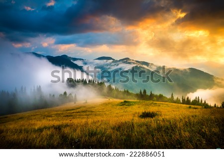 Amazing mountain landscape with fog and a haystack - stock photo