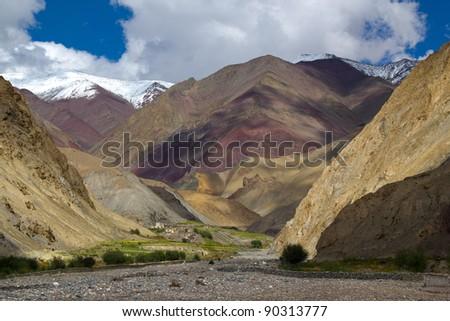 Amazing mountain landscape with small village under big Himalaya mountains - stock photo