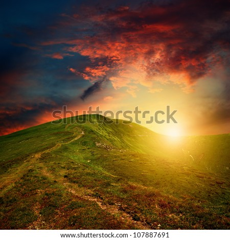 amazing mountain sunset with red clouds over the green hill - stock photo