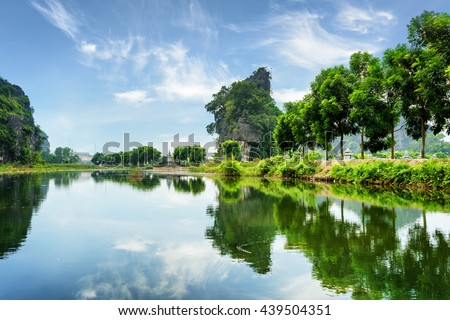 Amazing natural karst towers and green trees reflected in water of the Ngo Dong River at the Tam Coc portion, Ninh Binh Province, Vietnam. The Tam Coc is a popular tourist attraction in Asia.