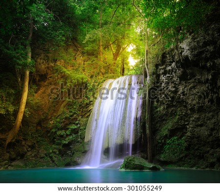 Amazing nature place. Sunlight beams and rays shining through wild jungle forest trees and plant leaves around tranquil waterfall falling in natural pond  - stock photo