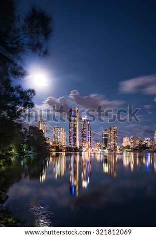 Amazing Night Exposure Of The Full Moon Brightening The Iconic Gold Coast City Tourist Skyline With A Reflection In The Calm Peaceful Water And Silky Clouds, Surfers Paradise, Queensland, Australia - stock photo