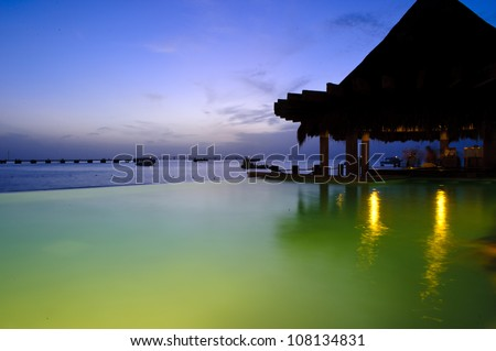 Amazing night shot of the bar at the swimming pool in a caribbean resort. Cozumel island in Mexico. - stock photo