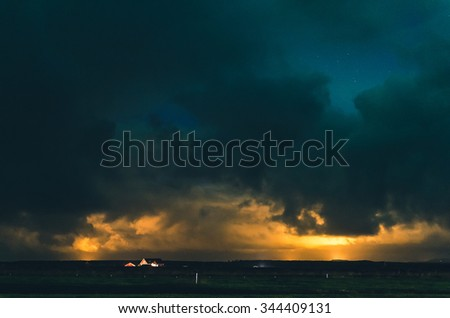 amazing night sky with orange glow and heavy clouds - stock photo