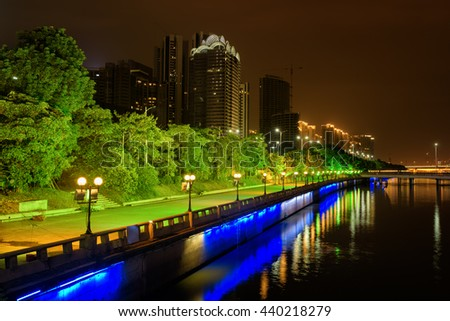 Amazing night view of the Pearl River waterfront at the Zhujiang New Town in Guangzhou, China. Beautiful cityscape with green trees. Blue and white night lights reflected in water.