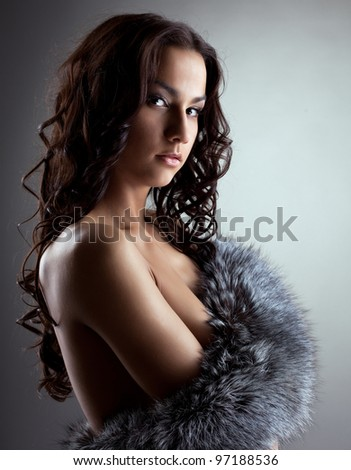 Amazing nude woman hiding breast by fur