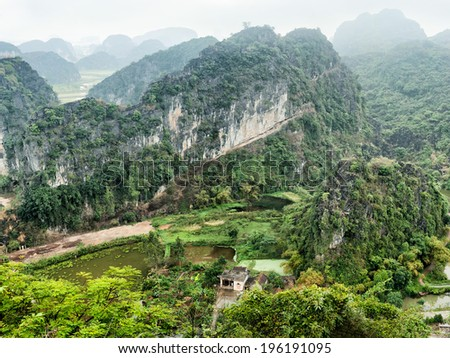 Amazing panorama view of Vietnamese village among rice fields and limestone rocks at the early morning. Ninh Binh, Vietnam. Travel landscapes and destinations background - stock photo