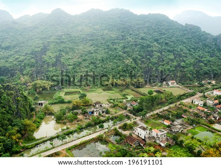 Amazing panorama view of Vietnamese village among rice fields and limestone rocks at the early morning. Ninh Binh, Vietnam. Travel landscapes and destinations background