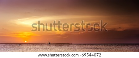 amazing panoramic seascape with a sail boat on horizon and sunset lighting up cloudscape - stock photo