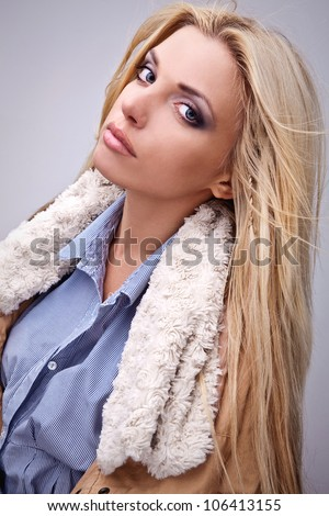 Amazing portrait of beautiful young blond woman on fur.