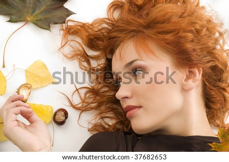 amazing portrait of red haired woman laying down on white floor with autumn leaves all around