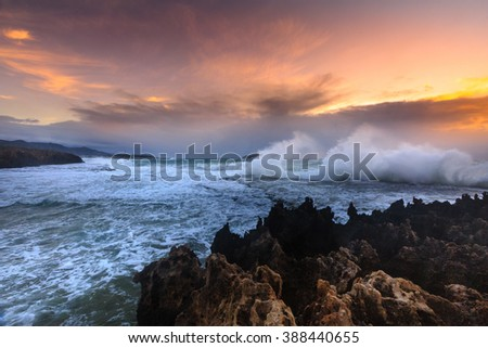 Amazing power of waves crashing against the rocks at dawn - stock photo