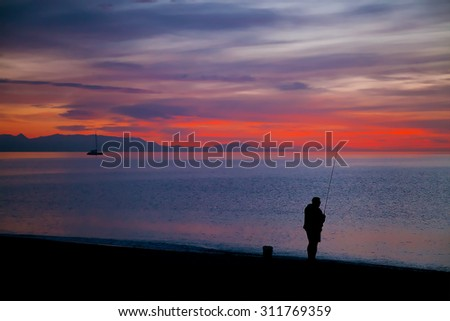 Amazing red-orange sunrise at sea with a silhouette of a fisherman and a distant yacht (sunrise dawn lighting) - stock photo