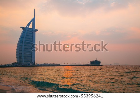 Amazing romantic Dubai view with a luxury Burj Al Arab hotel in the background during sunset over the sea.