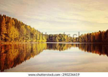 Amazing scenery in Finland during autumn by the lake with all the colors in the trees. Image has a vintage effect. - stock photo