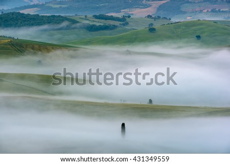 Amazing scenery of idyllic countryside with rolling hills veiled in morning fog. Aerial view of hill on a foggy spring morning - stock photo