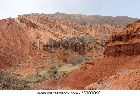 Amazing scenic orange hills, screes of sandstone, sides carved away by erosion, canyon Uchterek, Kyrgyzstan. - stock photo
