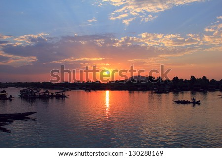 Amazing scenic view - colorful sunset with dramatic cloudy blue sky above calm water of Dal Lake and traditional boat (shikara) shadow figures, Srinagar, Jammu & Kashmir, Northern India, Central Asia