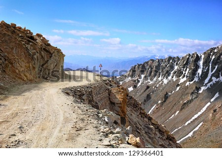 Amazing scenic view of high mountain road in rugged rocks covered with melting snow against the background of dramatic blue sky, Leh district, Ladakh range, Himalayas, Jammu & Kashmir, Northern India - stock photo