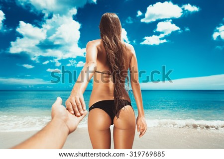 amazing sexy girl holding hand and walking on the beach. follow me. girl with fitness body with fit buttocks.