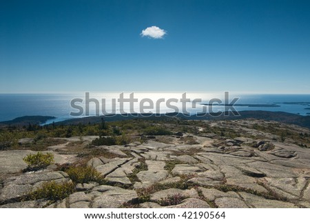 Amazing shoreline landscape with a single cloud hanging over the  calm ocean - stock photo