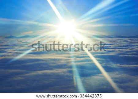 Amazing sky view from plane on blue sunset, sun and clouds - stock photo