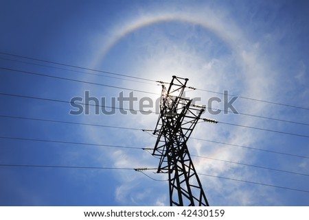Amazing sun halo above high-voltage power supply network - stock photo