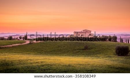 Amazing sunset and farmhouse in Tuscany, Italy - stock photo