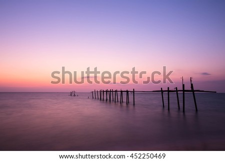 Amazing sunset beach. Long exposure bride wood and colorful suns