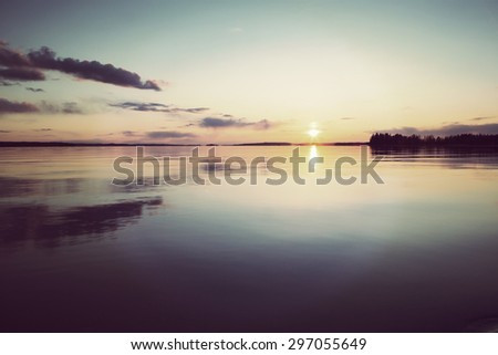 Amazing sunset by the lake. Colorful sky with dramatic clouds. Image has a vintage effect applied to create some artistic flavor. - stock photo