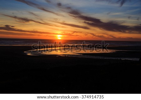 Amazing sunset on the D River Beach in Lincoln City Oregon, home of the world's shortest river that flows into the ocean. - stock photo